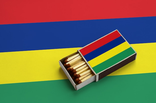 Mauritius flag  is shown in an open matchbox, which is filled with matches and lies on a large flag