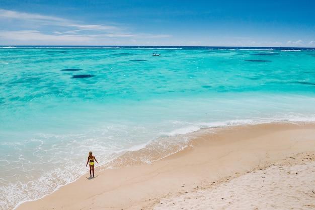 모리셔스, 인도양-낙원 섬 모리셔스를 방문하는 전 세계 관광객들과 함께 해변을 따라 걷는 소녀의 초상화.