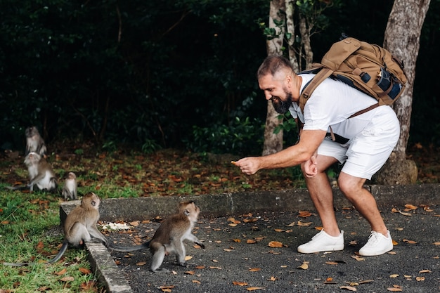 Mauritius island. a tourist with a backpack feeds monkeys by the side of the road in the jungle.