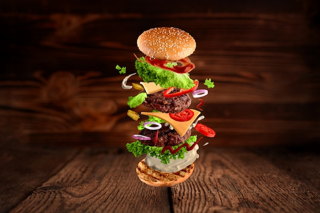 Maxi hamburger, double cheeseburger with flying ingredients isolated on wooden background.