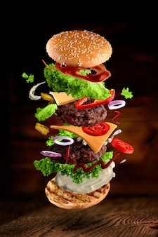 Maxi hamburger, double cheeseburger with flying ingredients isolated on wooden