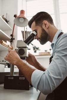 최대 정확도. 작업장에서 현미경으로 반지를 바라보는 남성 보석상의 측면. 사업. 보석 장비. 부속품