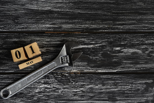 May 1 text wooden block calendar and adjustable wrench on black wooden background.
