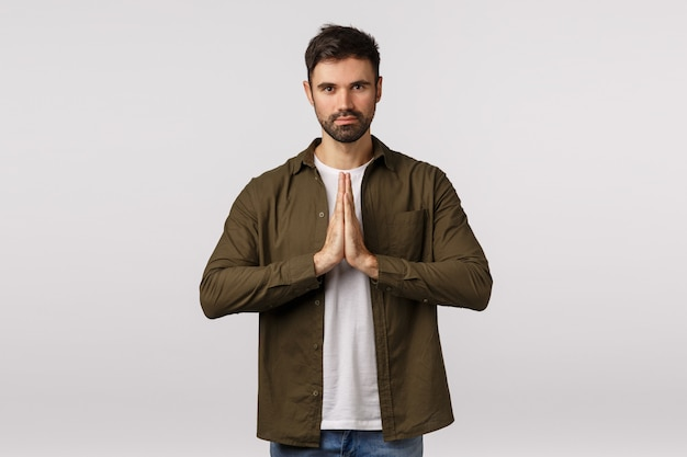 May the force be with you. confident and patient good-looking bearded man practice yoga, press palms together in namaste, praying gesture smiling peaceful and relaxed, meditating, bowing politely