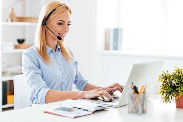 도와드릴까요? 헤드폰을 끼고 노트북 작업을 하고 작업장에 앉아 웃고 있는 쾌활한 젊은 미녀