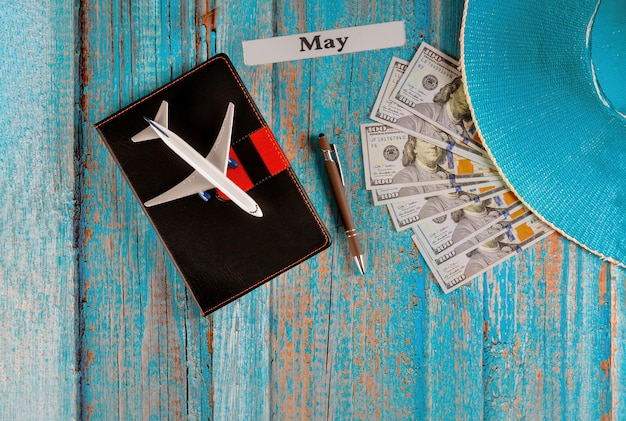 May month of calendar year, travel tourism planning airplane, pencil, blue hat and notebook with preparation for traveling