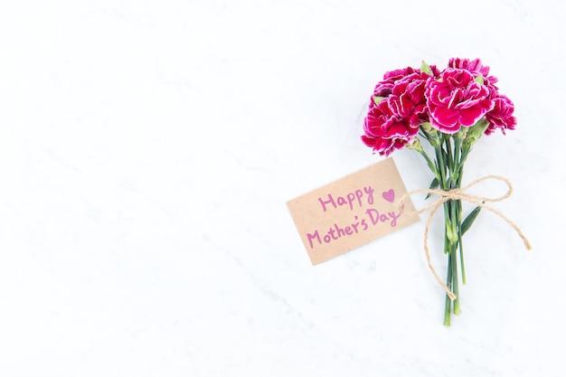 5月母の日のアイデアコンセプト写真-明るいモダンなテーブル、コピースペース、フラットレイ、上面図、モックアップで分離されたクラフトテキストカードと弓で結ばれた美しい咲くカーネーション