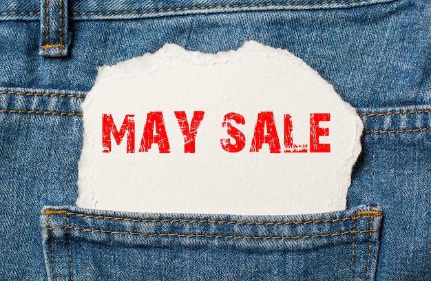 Майская распродажа на белой бумаге в кармане джинсов синих джинсов