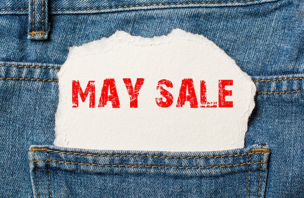 May sale on white paper in the pocket of blue denim jeans