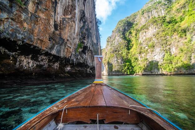 Традиционный деревянный длиннохвостый нос шлюпки такси с цветками и лентами украшения на maya bay приставает к берегу против крутых холмов известняка. основная туристическая достопримечательность таиланда, остров ко пхи пхи лех