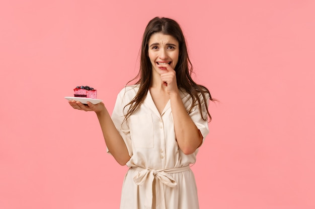 Maybe just one bite. tempting and eager brunette woman want try tasty piece cake, holding dessert frowning and biting fingernails from desire to eat sweets, resist trying stick diet, pink wall