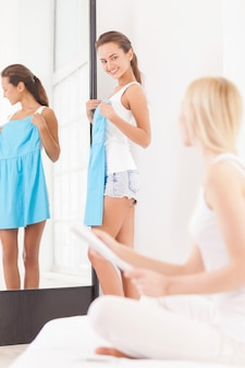 多分このドレス?青いドレスを着て鏡の近くに立って、雑誌で前景に座っている別の女性を見ている美しい若い女性