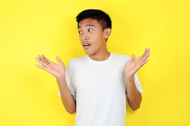 예 또는 아니요. 의심스러운 젊은 아시아 남자는 당황하여 어깨를 으쓱하고, 결정을 내리려고 하고, 원하는 것을 어리둥절하고, 노란색 배경 위에 고립되어 있습니다. 망설임과 불확실성
