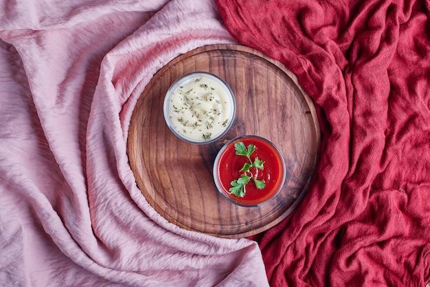Maionese e ketchup in coppe di vetro in un piatto di legno.