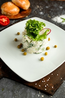 Салат майонезный с зеленым горошком на белой тарелке