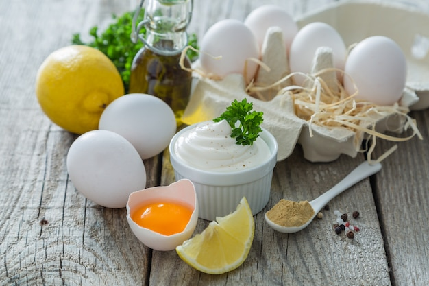 Mayonnaise sauce and ingredients on wood table
