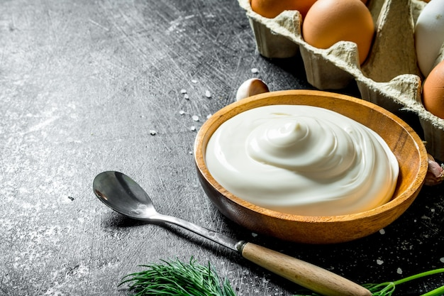 Mayonnaise with fresh eggs. on dark rustic