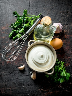 Mayonnaise with herbs, oil and garlic. on dark rustic