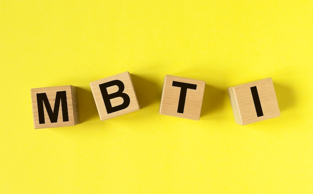 Mbtiの頭字語、黄色の背景に木製のダイスの碑文