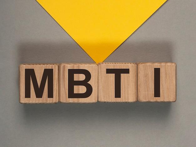 灰色と黄色の背景の木製の立方体のmbtiの頭字語。心理テスト。