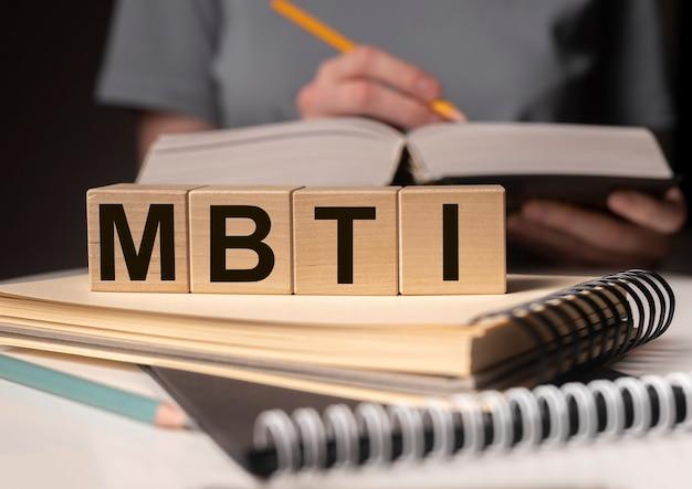 Mbtiの頭字語、本のある机の上の木のブロックの言葉。心理学の研究と研究の概念。