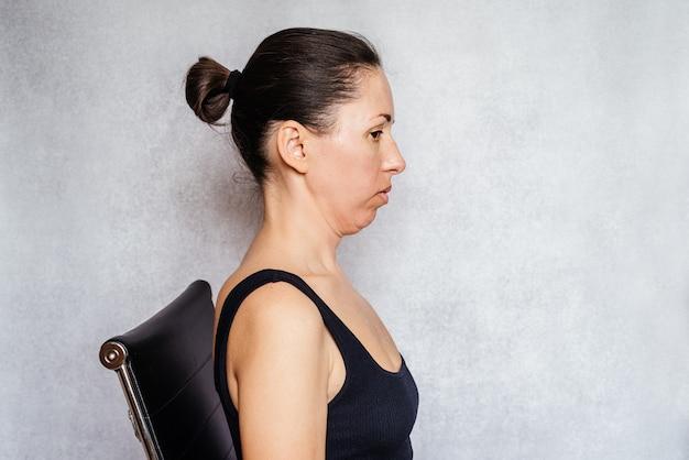 목 통증을 완화하는 mckenzie 방법 운동, 목 통증 완화 운동을 하는 동안 한 여성이 수축된 자세로 머리를 잡고 있습니다
