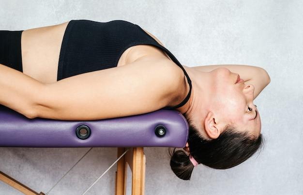 목 통증을 완화하는 맥켄지법 운동 마사지 테이블에 누워서 그녀를 낮추는 여성