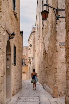 Туристская женщина гуляя в переулок улицы mdina, безмолвного города. мальта.