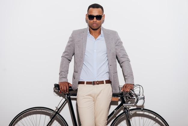 나와 내 자전거. 그의 복고풍 스타일의 자전거에 기대어 선글라스에 자신감이 젊은 아프리카 남자