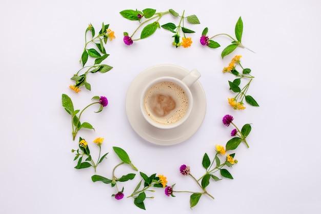牧草地の花と野花がコーヒーカップで輪になって配置されています。フラットレイ。