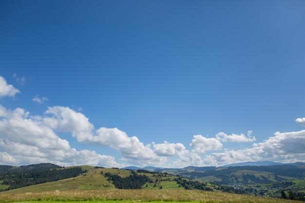 牧草地、山と雲と青い空