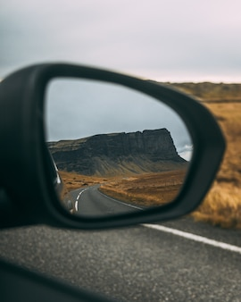 Meadow surrounded by rocks near the road under a cloudy sky reflecting on a rear-view mirror