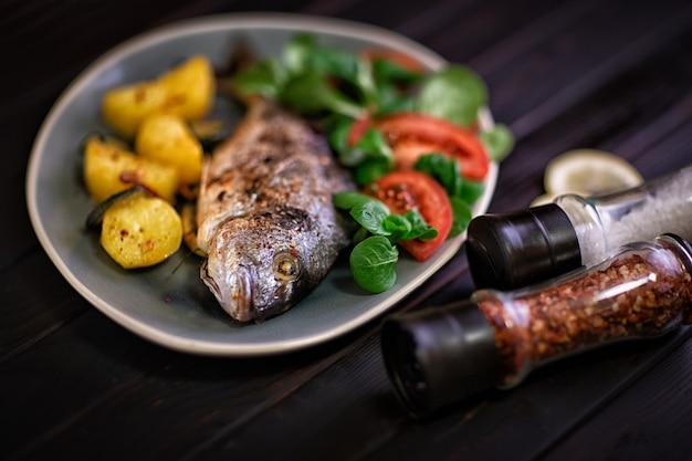Еда. запеченная рыба дорадо с овощами в духовке на темном фоне.