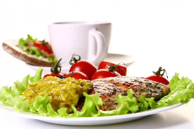 Meal garnish with filet and vegetables and coffee