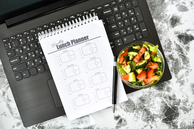 A meal plan for a week and bowl with vegetable salad in the workplace near the computer