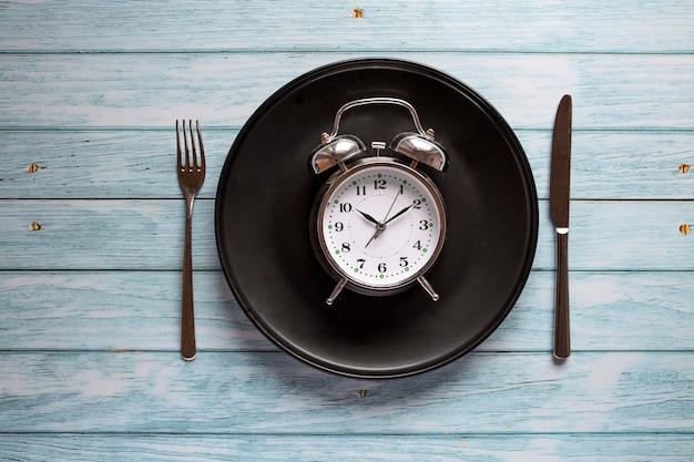 Meal planning for diet concept , intermittent fasting concept with clock on plate, fork and knife on wooden table