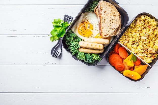 Еда готовит контейнеры с рисом с курицей, запеченными овощами, яйцами, сосисками и салатами.