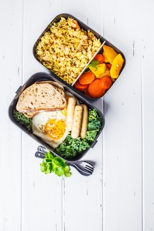 Meal prep containers with rice with chicken, baked vegetables, eggs, sausages and salad overhead shot.