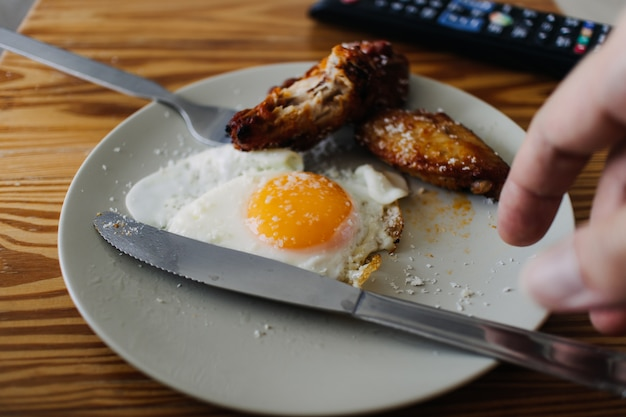 Meal set of fried egg and fried chicken wings. concept of eating in living room.