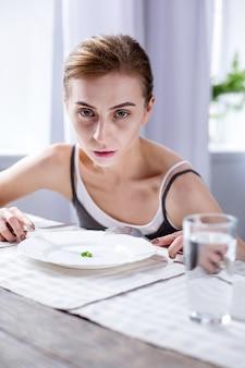 식사 시간. 그녀의 식사를 먹는 동안 테이블에 앉아 쾌활한 창백한 여자