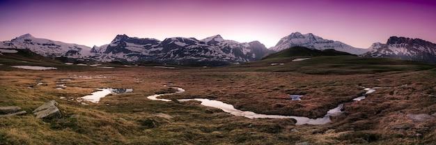 フレンチアルプスの背景に雪に覆われた山々と秋の蛇行