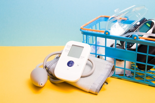Measure blood pressure monitor lies next to a small blue shopping basket in which there is a glucose meter and a nebulizer for inhalation