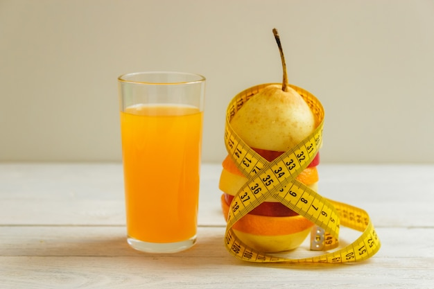 Measure tape and fresh fruit on wooden table. healthy lifestyle diet with fresh fruits.