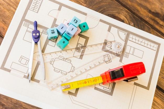 Measure tape, ruler, divider and math blocks on blueprint