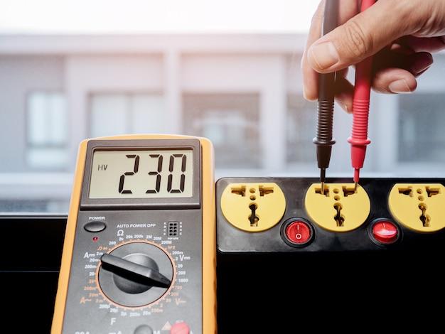 デジタルメーターで電源コンセントから230ボルトのac電圧を測定します。