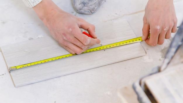 家のタイルの修理を測定します。セレクティブフォーカス。