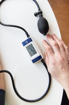 혈압 측정. 여자는 혈압을 측정합니다. 집에서 자가 진단. 위에서 볼 수 있습니다. 건강 및 관리 개념입니다.