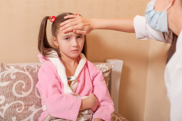Measurement of temperature to the little child. doctors hand on girls forehead.