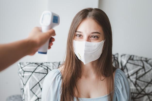 Измерение температуры молодой женщины в маске с помощью инфракрасного термометра для проверки людей с лихорадкой для предотвращения распространения коронавируса