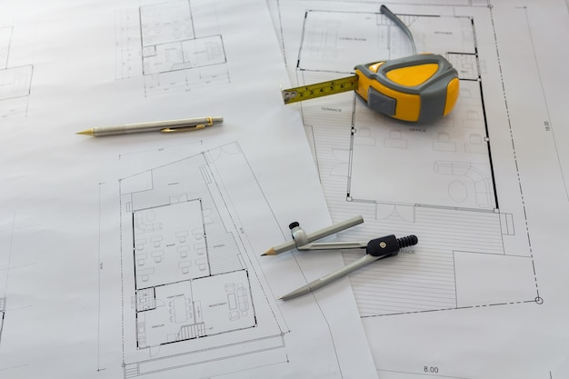 Measurement tool and dividers or compasses on blueprint, architectural concept